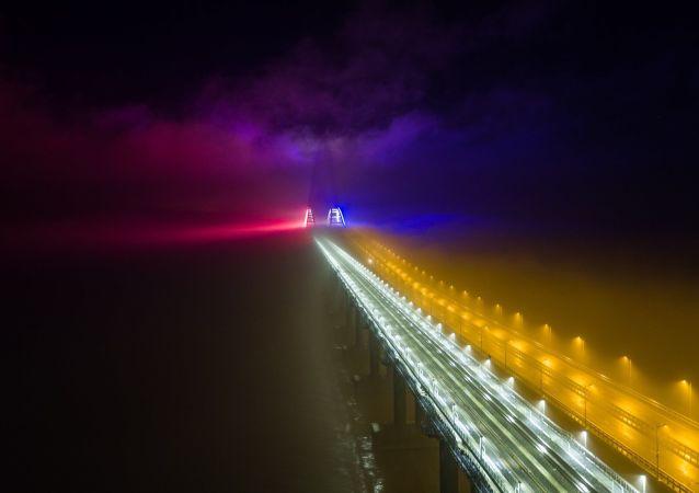 El puente de Crimea iluminado con luces coloridas durante la noche