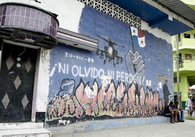 Dos hombres frente a un mural que representa la invasión estadounidense de Panamá en el barrio de Chorrillo en la ciudad de Panamá