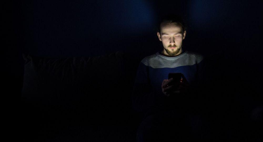Un hombre sostiene un móvil en la oscuridad