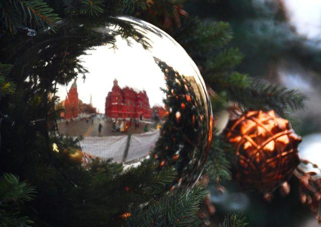 Los muros de la Plaza Roja de Moscú reflejados en un adorno navideño