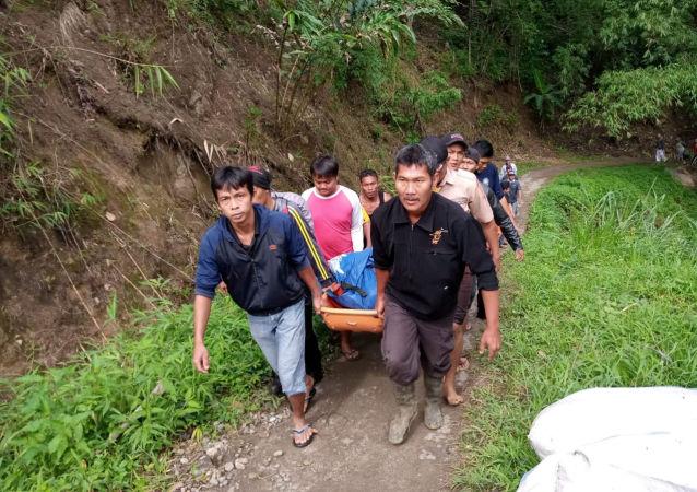 Rescatistas indonesios con un cuerpo