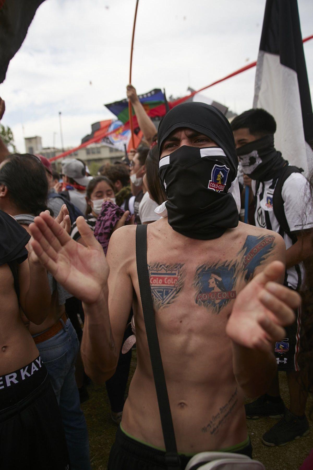 Manifestante con tatuajes y camiseta de Colo Colo