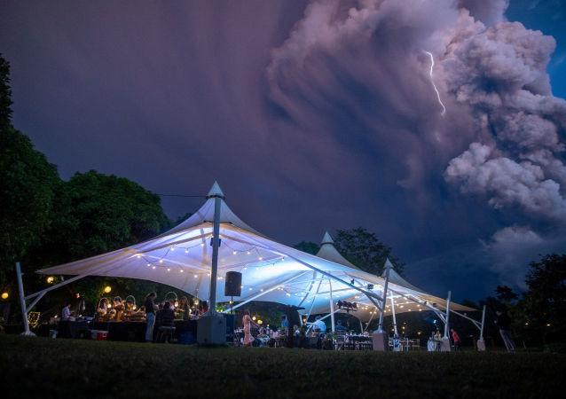 La gente asiste a una ceremonia de boda mientras el volcán Taal envía una columna de ceniza al fondo