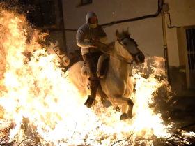 Jinetes cabalgan a través del fuego en la fiesta de las Luminarias