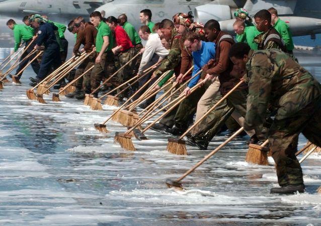 Militares estadounidenses limpian la cubierta de un portaaviones