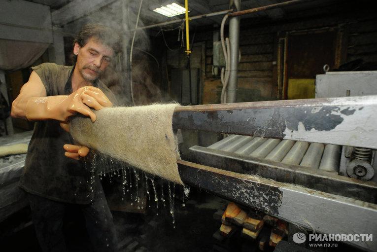 Рабочий обрабатывает валяное изделие на вертикально-растяжном станке