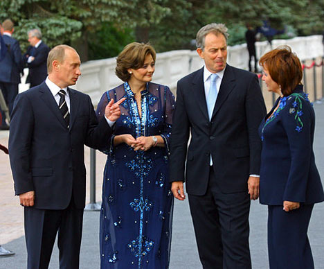 El presidente de Rusia, Vladimir Putin, con la esposa, y el primer ministro de Gran Bretaña, Antony Blair, con la esposa (de izquierda a derecha), antes de comenzar el almuerzo extraoficial de los Jefes de Estado y Gobierno. Daba la impresión de que el azul era el color principal de la reunión. De este color precisamente eran los trajes de los Putin. Pero el de Liudmila era más ingenioso, en la parte delantera y las mangas de su chaqueta estaban fijadas flores de aciano, con tallos y hojas verdes. El maquillaje y los accesorios de la primera dama también estaban al tono: los ojos, matizados con sombras azules, y de las orejas pendían zarcillos adornados con piedras de un azul celeste. Cherry Blair vestía un pantalón de color lila oscuro y un top, sobre el cual estaba puesto un vestido transparente largo de muselina, ricamente adornado con lentejuelas azules. Tony Blair tenía corbata azul.